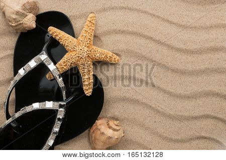 Black flip-flops with rhinestones and seashell starfish on the wavy sand. With place for your text
