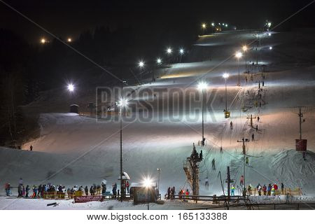 5 January 2017. Zuberec Ski Park. Slovakia. Western Tatras. Europe. Ski with the lift at night lit by lanterns. Night skiing. Adults and children skiing after work. Promoting a healthy active lifestyle.