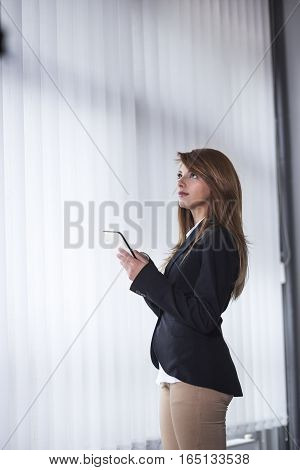Portrait of beautiful business woman standing next to the window in her office, holding a tablet computer