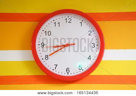 wall orange clock on colorful wall. white watch