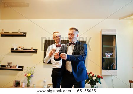 Best Man Helping Wear Groom On His Wedding Day.