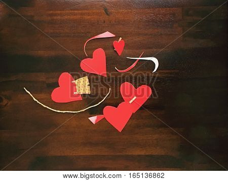 Vintage red paper hearts on dark wood background Valentine's Day share image with room for copy promotion hashtag or message space making Valentine's cards love from above. Part of series