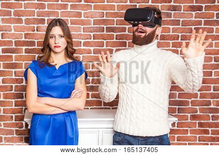 VR technology and conflict between couple. man using vr headset and his wife is angry.
