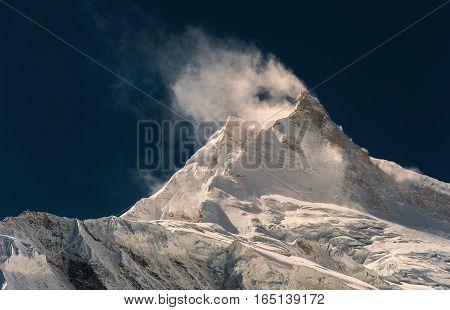 Wind blowing snow from mountain peak. Nepal, Manaslu