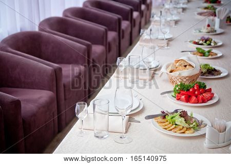 a table covered with a white tablecloth with salads glasses plates napkins and a number of seats