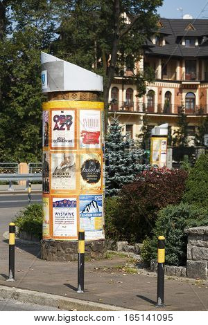 ZAKOPANE POLAND - SEPTEMBER 15 2016: Advertising column placed in a city. An advertising column presents posters and billboards on it. Advertising pillar is one way of outdoor advertising