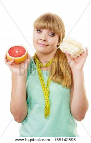 Woman with measuring tape holds in hands cake and grapefruit choosing deciding between sweet food or fresh fruit make dietary choice. Weight loss diet dilemma concept. Isolated on white poster