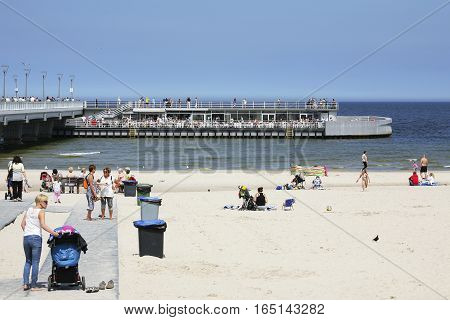KOLOBRZEG POLAND - JUNE 19 2016: In the cafe on the pier is a lot of people. On a sandy beach on the the sea shore a few vacationers spend their time