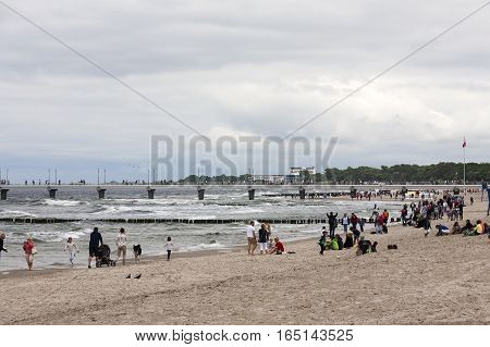 KOLOBRZEG POLAND - JUNE 26 2016: Vacationers enjoy a cloudy and windy day on the sandy beach and they are walking along the coast of the Baltic Sea or they sit on the sand