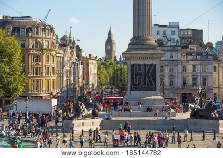 LONDON, UK - SEPTEMBER 10, 2015:  Big Ben and houses of Parliament view from the Trafalgar square with lots of people on the square