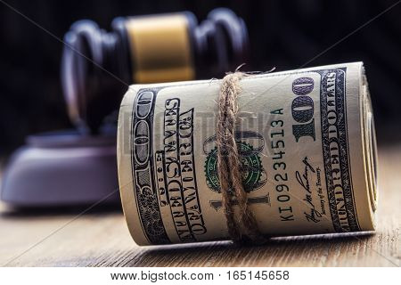 Judge's hammer gavel. Justice dollars banknotes and usa flag in the background. Court gavel and rolled banknotes. Still life of a bribery corruption in the US judicial system.