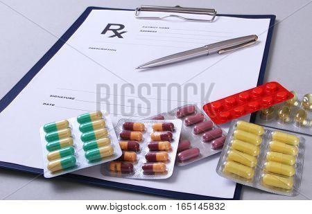 Closeup of a pils, stethoscope, pen on an rx prescription