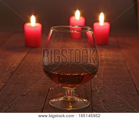 glass of wine or cognac and red candle on a wooden background