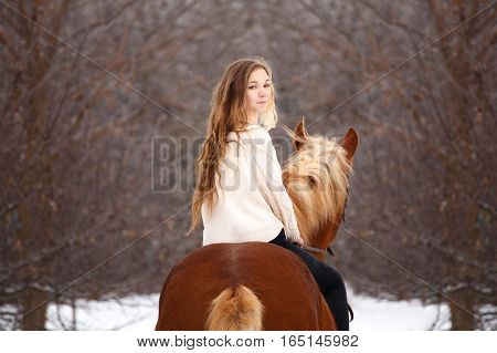 Cute girl looking back over shoulder riding horse in forest