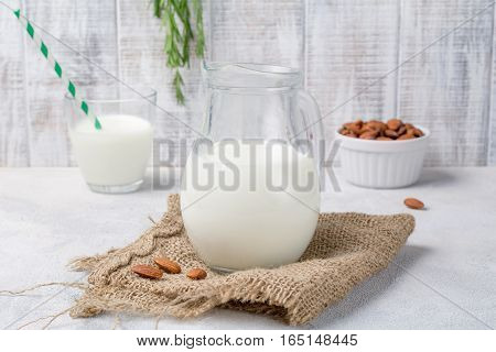 Fresh almond milk in jug on rustic textile. Healthy vegan dairy free milk substitute. Close up view
