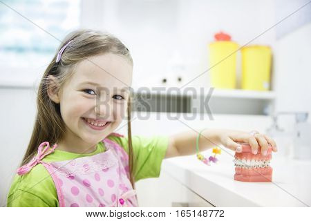 Little girl holding an artificial model of human jaw with dental braces in orthodontic office smiling. Pediatric dentistry aesthetic dentistry early education and prevention concept.