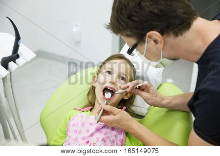 Child patient sitting on dental chair in paediatric dentists office on her regular checkup for caries and gum disease. Early prevention oral hygiene and milk teeth care concept.