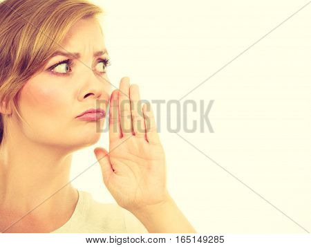 Woman whispering in funny way with hand close to mouth.