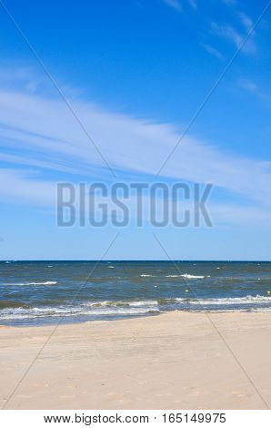 Recreation sea travel cruise and relax concept. Deserted beach in Palanga Lithuania. Yellow sand on beach near blue sea.