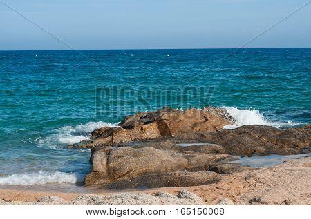 Deep dark blue sea waves breaking on a rocks at Lloret de mar beach Spain. Sea waves near cliff. White foam of a sea wave.