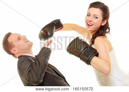 Married couple fighting with each other. Woman wearing wedding dress and boxing gloves punching her husband in elegant suit.
