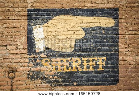 a sign indicating the location of the Sheriff painted on a wall