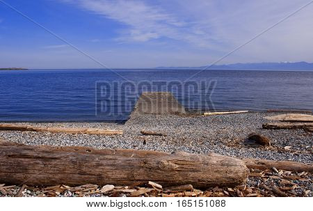 A cement jetty at a rocky west coast beach.