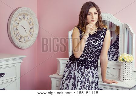 Beautiful girl in her room and posing near dressing table, looking at camera.