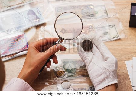 Woman Looks At The Coin With A Magnifying Glass