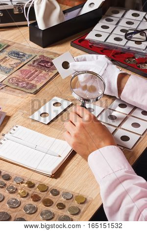 Woman Looks At The Coin Through A Magnifying Glass