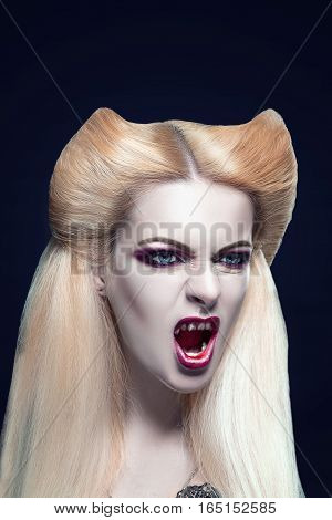 Beautiful blonde girl vampire with  blood is on the mouth and eyes. Amazing hairstyle