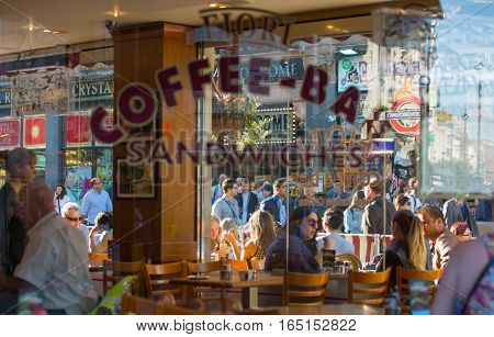 LONDON, UK - OCTOBER 4, 2015: People in the cafe behind glass reflection. Leicester square the famous destination for restaurants and bars