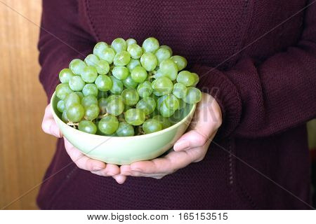Female hands hold green  bowl with appetizing grape closeup