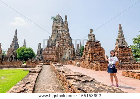 Tourist teenage girl show hand inviting to visit Wat Chaiwatthanaram is buddhist ancient temple famous and major tourist attraction religion Phra Nakhon Si Ayutthaya Historical Park Thailand