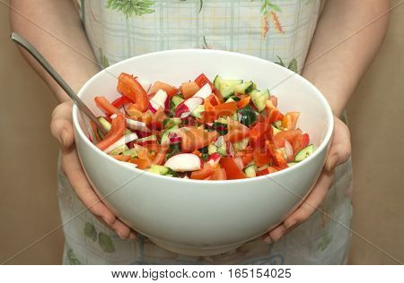 Housewife in fabric apron holds big white china bowl with appetizing vegetable salad closeup