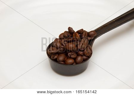 Spoon with coffee grains on a white background, breakfast
