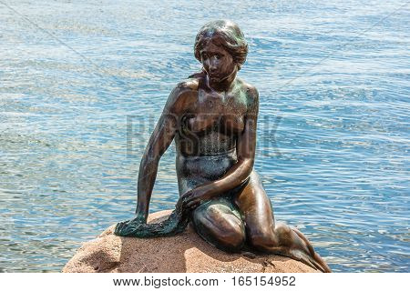 Copenhagen, Denmark, July 13, 2016 - Famous little mermaid in Copenhagen sitting on a stone in the the blue sea. The statue is the number one landmark in Copenhagen.