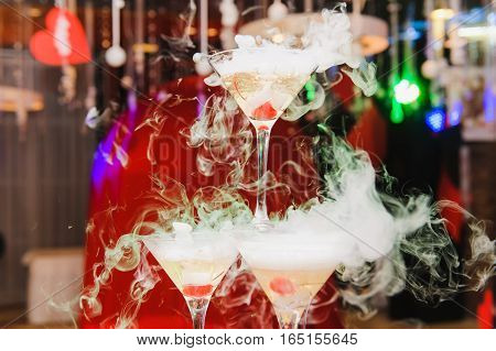 Pyramid of the martini glasses for event, party with smoke. Dry ice in a glass