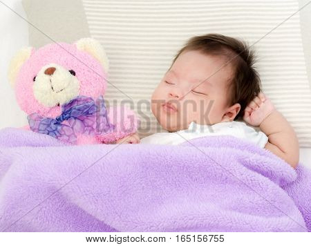 Portrait Of Adorable Baby Girl Sleeping On The Bed With Bear Doll And Copy Space
