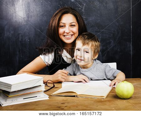 little cute boy with teacher in classroom, real people