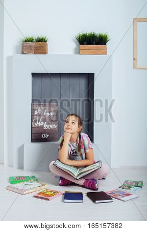 The child thinks schoolgirl sitting and reading a book. The concept of childhood training and education.