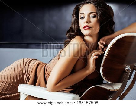 beauty yong brunette woman sitting near fireplace at home, winter warm evening in interior, waiting to celebrate