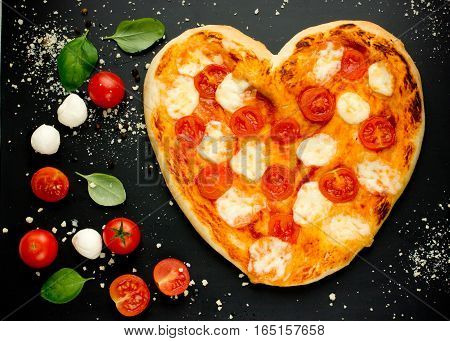 Heart-shaped pizza with cherry tomatoes mozzarella and basil on Valentines Day on a black background with ingredients