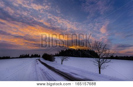 Snowy landscape and road at sunset. Moravian landscape Tasovice.