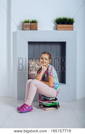 Girl schoolgirl sitting on book and laughs. The concept of childhood training and education.