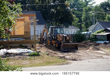 HARBOR SPRINGS, MICHIGAN / UNITED STATES - AUGUST 4, 2016: A Case bulldozer moves dirt at a residential construction site in Harbor Springs.