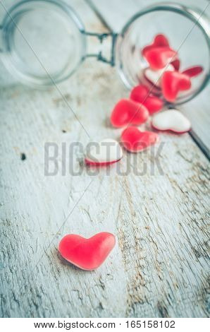 Red heart shape candy in a glass jar on a white rustic wooden table with space for text. Romantic love concept. Valentine's Day greetings card. Valentines theme. Selective focus. Copy space.
