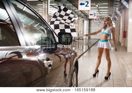 Hot leggy model at car wah service. Seductive woman in uniform and high heels posing to camera with checkered race flag
