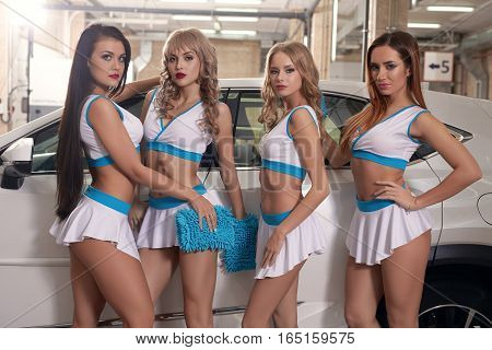 Beautiful young sexy models wearing uniform posing to camera at carwash service while standing in front of luxury car