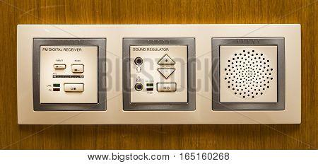 a modern FM digital radio receiver on a wooden wall